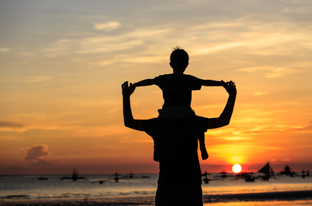 Foto de father and son on sky at sunset beach - Imagen libre de derechos