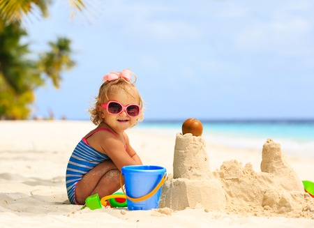 Foto de cute little girl playing with sand on tropical beach - Imagen libre de derechos