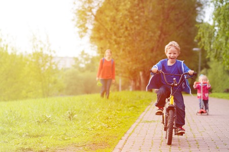 Foto de happy kids riding scooter and bike in the park, family sport - Imagen libre de derechos