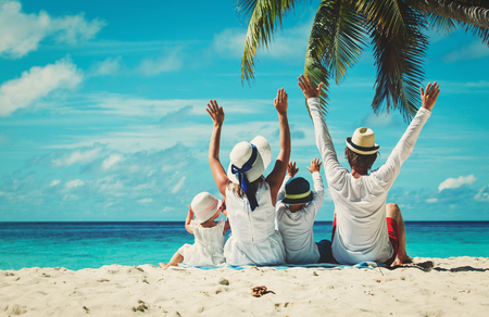 Foto de happy family with two kids hands up on the beach - Imagen libre de derechos