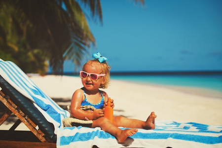 Photo pour cute little girl with sunblock cream on beach - image libre de droit