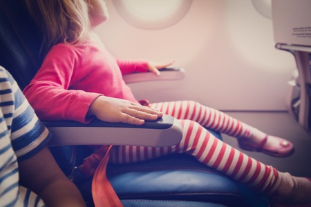 Photo pour flight safety concept- little girl waiting to take off in plane - image libre de droit