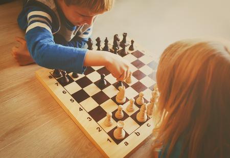 Photo pour little boy and girl play chess - image libre de droit