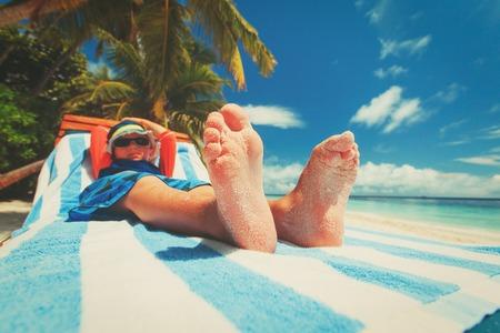 Photo pour little boy relax on tropical beach, focus on feet - image libre de droit