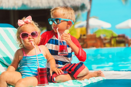 Foto de little boy and toddler girl drinking juices on beach - Imagen libre de derechos