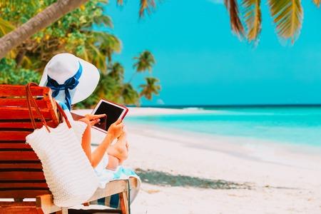 Photo pour woman with touch pad on tropical beach - image libre de droit