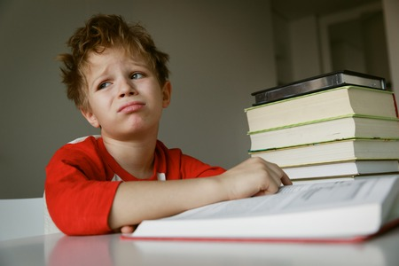 Foto de little boy tired stressed of reading, doing homework - Imagen libre de derechos
