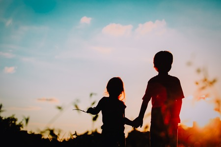 Foto de little boy and girl silhouettes holding hands at sunset - Imagen libre de derechos