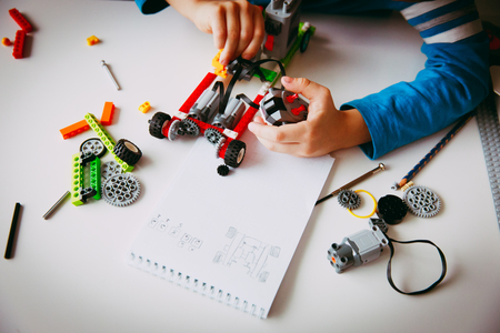 Photo pour little boy building robot at robotic technology school lesson - image libre de droit