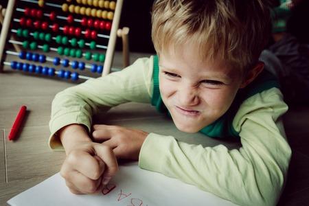 Photo pour little boy hates doing homework, stress and agreession - image libre de droit