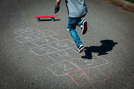 Photo pour little boy playing hopscotch on playground - image libre de droit