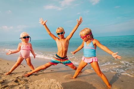 Photo pour happy kids- little girls and boy-play enjoy beach - image libre de droit