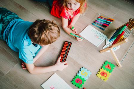 Foto de kids- boy and girl- learning numbers, arithmetic, abacus calculation - Imagen libre de derechos