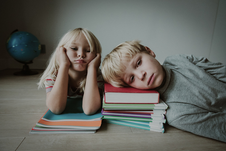 Photo pour little boy and girl bored tired stressed of doing homework - image libre de droit