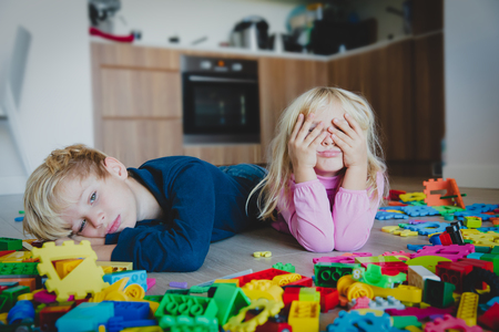 Foto de little boy and girl tired stressed exhausted with toys scattered indoors - Imagen libre de derechos
