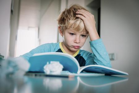 Photo pour difficult homework- little boy having problems with reading - image libre de droit