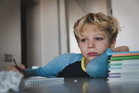 Photo pour little boy tired stressed of reading, doing homework - image libre de droit