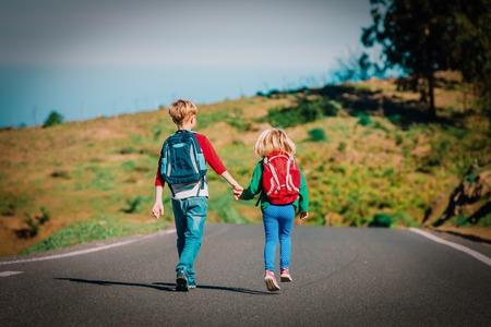 Foto de kids go to school - brother and sister with backpacks walking on road - Imagen libre de derechos