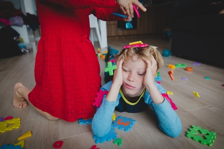 Photo pour kids play at home, scattered toys and tired exhausted boy - image libre de droit