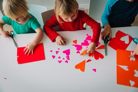 Photo pour kids making hearts from paper, prepare for valentine day - image libre de droit