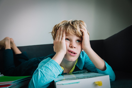 Photo pour little boy tired of reading, kid bored of doing homework - image libre de droit