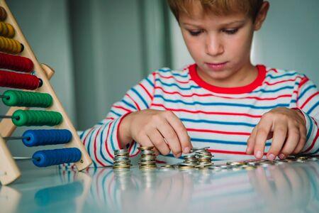 Foto de child counting money and make tower from coints, boy make savings - Imagen libre de derechos