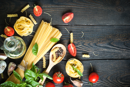 Foto de Ingredients for cooking Italian pasta - spaghetti, tomatoes, basil and garlic. - Imagen libre de derechos