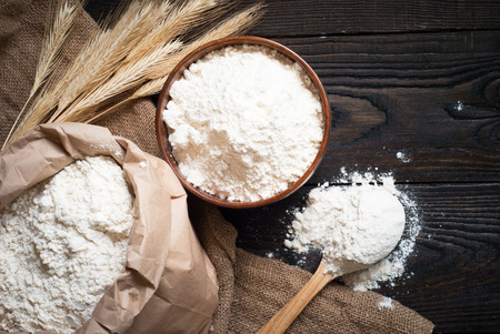 Foto de Flour in a wooden bowl, paper bag and spoon. Top view, space for text. - Imagen libre de derechos