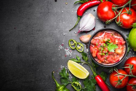 Foto de Traditional Latin American mexican  salsa sauce and ingredients on black stone table. Top view copy space. - Imagen libre de derechos