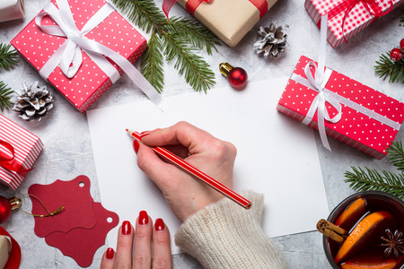 Foto de Christmas background. Woman packing Christmas present box and write wishes. Top view. - Imagen libre de derechos