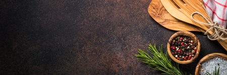 Foto de Food background with cooking utensils, cutting board, spices and herbs  on dark rusty stone table. Long banner format. - Imagen libre de derechos