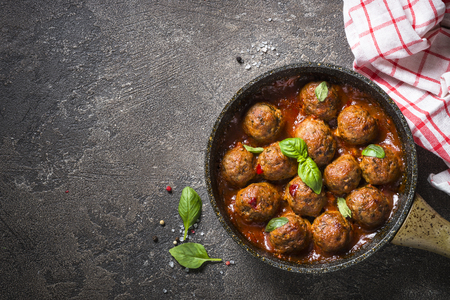 Photo for Meatballs in tomato sauce in a frying pan on dark stone table. - Royalty Free Image