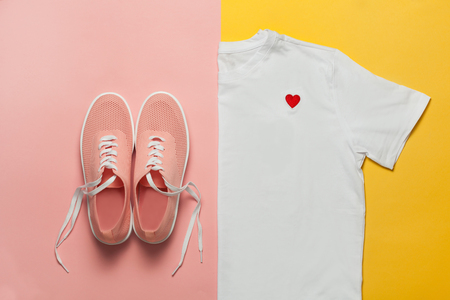 Foto de Top view of white woman t-shirt and pink shoes on pink and yellow background. Fashion clothes set. Flat lay. Place for text. 90's style. - Imagen libre de derechos