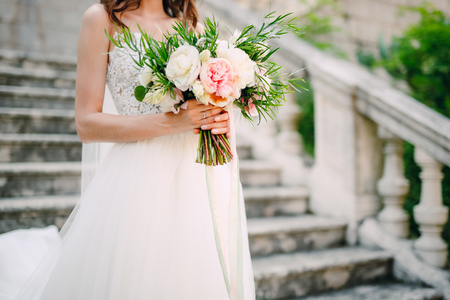 Photo pour Wedding bouquet of peonies in the hands of the bride. Wedding in Montenegro. - image libre de droit