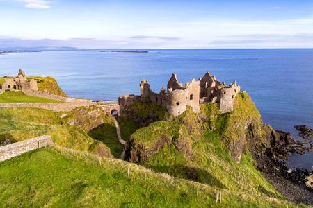 Foto de Ruins of medieval Dunluce Castle on a steep cliff. Northern coast of County Antrim, Northern Ireland, UK. Aerial view. - Imagen libre de derechos