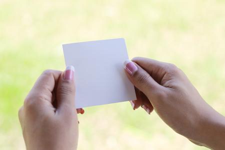 Foto de hand holding a piece of blank torn paper on grass background - Imagen libre de derechos