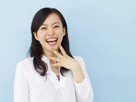 Happy young japanese girl showing victory sign isolated on blue background