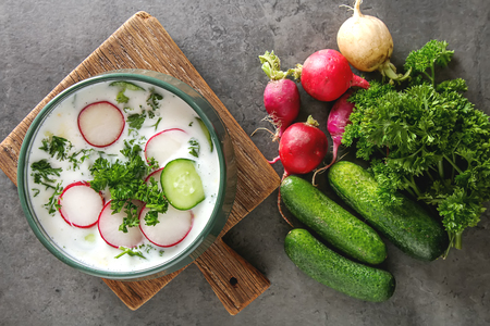 Photo for Summer cold soup - okroshka in a ceramic bowl. Ingredients of potatoes, radishes, cucumbers, parsley, eggs. Dark background - Royalty Free Image
