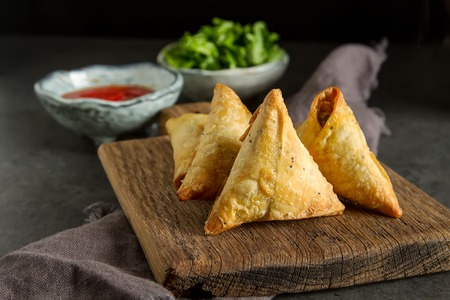Photo pour Asian food. Vegetarian samsa with tomato sauce and herbs. Dark background - image libre de droit