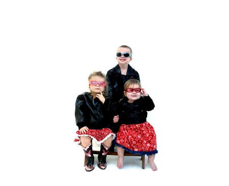 Three small children model leather coats and cool sunglasses   Two sisters are sitting on a wooden bench with brother standing behind   Two are smiling and one is not so sure