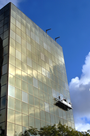 Photo pour Scaffolding lifts workers cleaning exterior windows on a building in Hancock, Michigan.  Vivid blue sky and clouds are reflected in office window glass. - image libre de droit