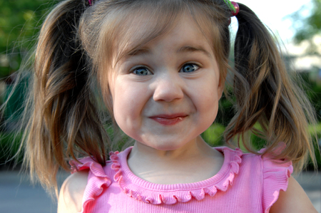 Foto für Little girl tries to hold in her giggles as she puts her face into a mirthful smirk.  She has pigtails and a pink shirt. - Lizenzfreies Bild