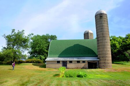 Foto de Woman stands besides a green roofed dairy barn with two tall silos.  Compared to young woman's size, dairy barn is huge. - Imagen libre de derechos