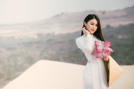 Photo for Beautiful Vietnamese holding Pink Lotus in White Sand dune desert, Muine, Vietnam - Royalty Free Image