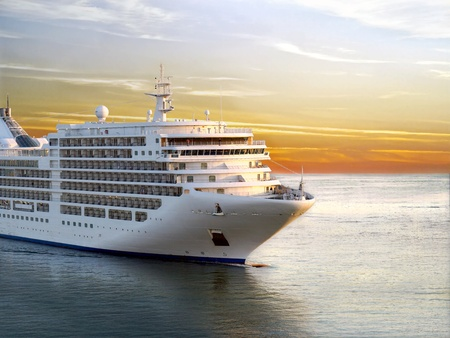 Luxury cruise ship sailing from port on sunset