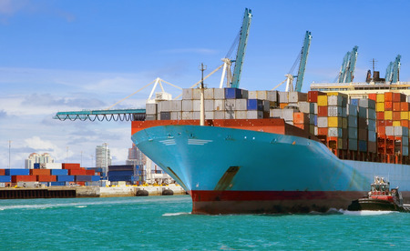 Foto per Large cargo ship with many shipping containers sailing from port - Immagine Royalty Free