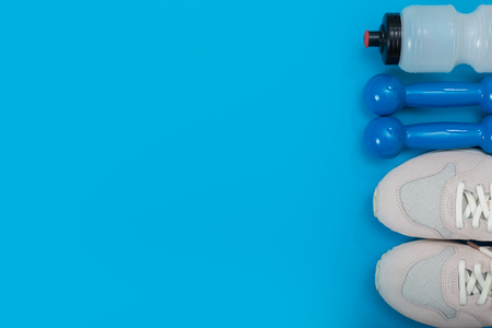 Sport equipment on blue background, top view. Concept healthy lifestyle, healthy food, sport and diet.