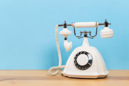 Foto de Vintage old white telephone on wooden table with color wall background - Imagen libre de derechos