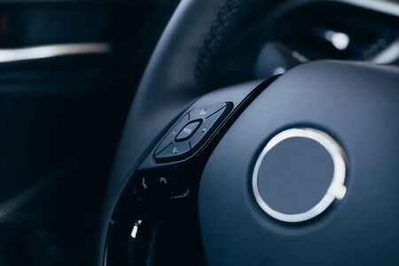 Photo for close up Modern black steering wheel with multifunction buttons Integrated stereo controls pushes the for quick control technology in the car. - Royalty Free Image