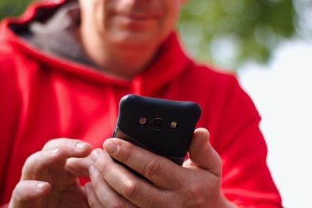 Foto de Man dressed in red sweatshirt uses a cell phone - Imagen libre de derechos